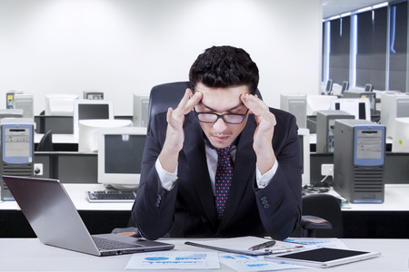 man working on computer: Caucasian businessman working in the office and feel headache
