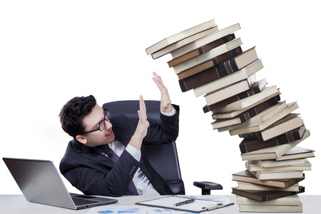 Portrait of overworked young businessman holds falling books on the desk photo