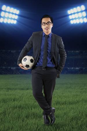 Full length of a young businessman standing at field while holding a soccer ball photo