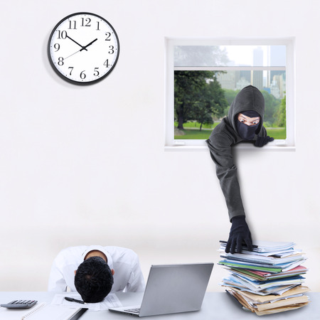 criminal activity: Criminal activity concept with male bandit wearing mask and steal corporate documents through the window Stock Photo