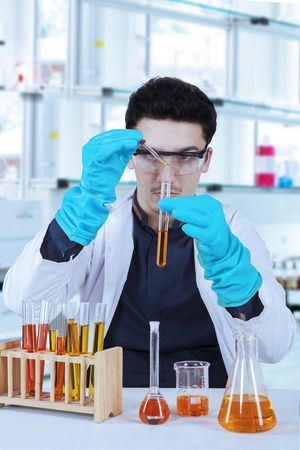 protective glasses: Young scientist with lab coat, gloves, and protective glasses doing experiment in laboratory