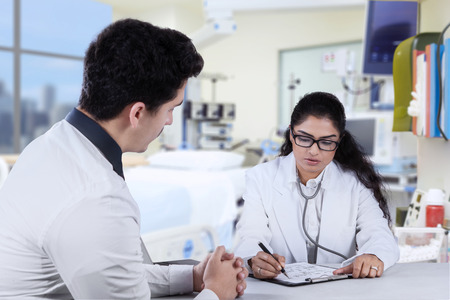 medical personal: Female doctor make a prescription for her patient after consulting in the hospital
