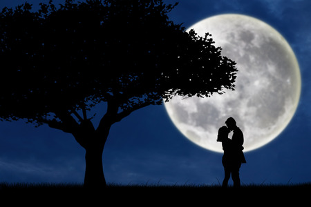 couple lit: Silhouette of couple kissing on blue full moon Stock Photo