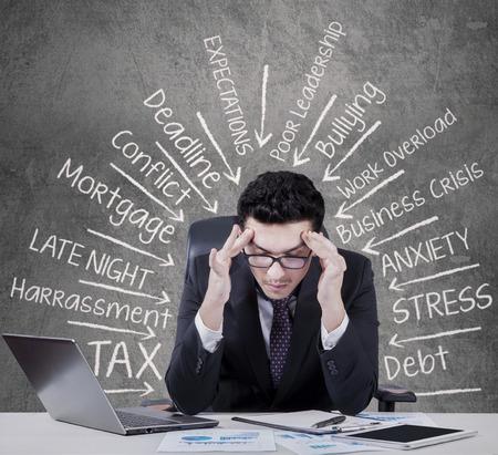 dolor de cabeza: Hombre de negocios cauc�sico joven que tiene dolor de cabeza cuando piensa soluci�n para sus problemas