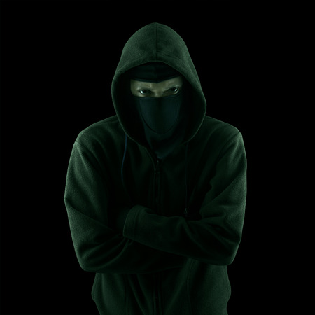 scary man: A thief with hoodie look ahead against a dark background