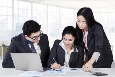 asian business team: Female entrepreneur signing a business contract with two partners looking her
