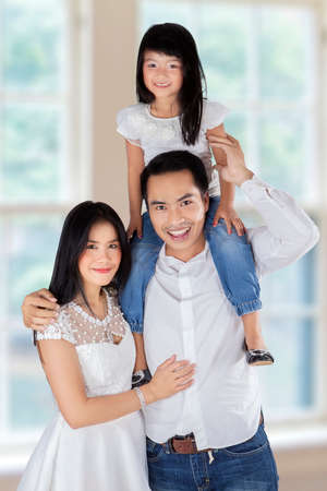 carry: Three member of happy family smiling at camera, shot at home