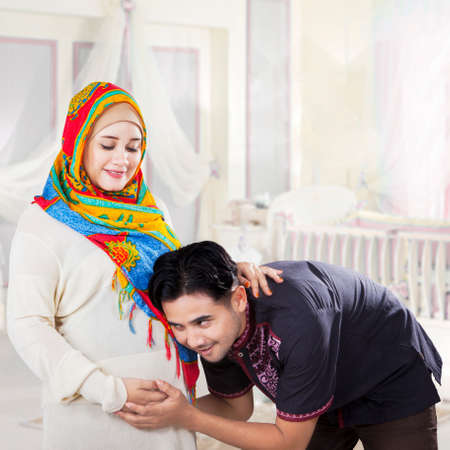 pregnant woman with husband: Portrait of muslim husband listeing his baby on wifes belly in the bedroom