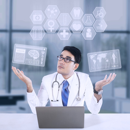 general insurance: Male doctor and medical icon, shot in hospital Stock Photo