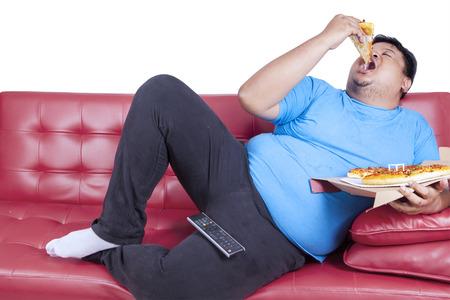 집에서 소파에 앉아있는 동안 체중 사람은 피자를 먹는다