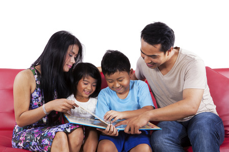 indonesian: Four member of happy family reading a story book together on sofa Stock Photo