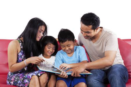Vier lid van gelukkige familie samen lezen van een verhaal boek op bank