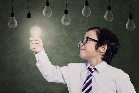 intelligent solutions: Smart asian child holding a lit bulb under lamps Stock Photo