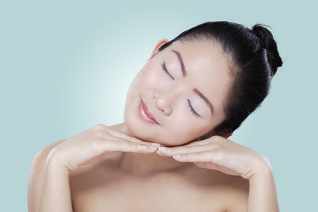 pampering: Attractive woman with beautiful skin relaxing on her hands after pampering her skin Stock Photo