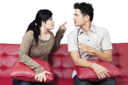 aggressive people: Portrait of young couple quarreling and blaming each other, isolated on white
