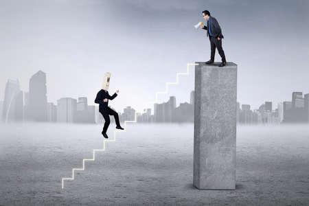 arrogancia: Empresario se ejecuta en las escaleras para encontrarse con su líder, llamado con un megáfono de la parte superior Foto de archivo