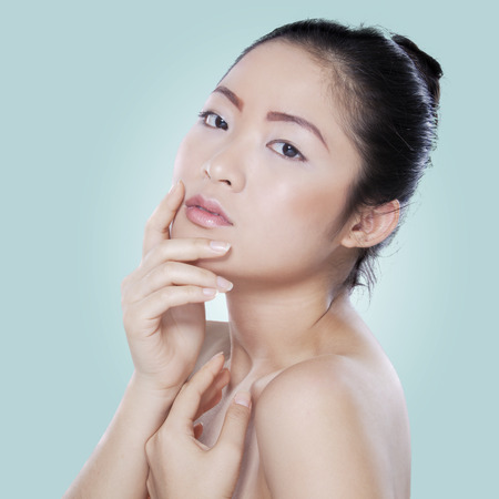 pampering: Young chinese woman with clean skin posing at the camera after pampering her skin