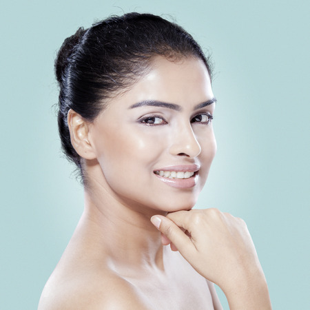 from side: Closeup of femal model with beauty face smiling at the camera in the studio against blue background