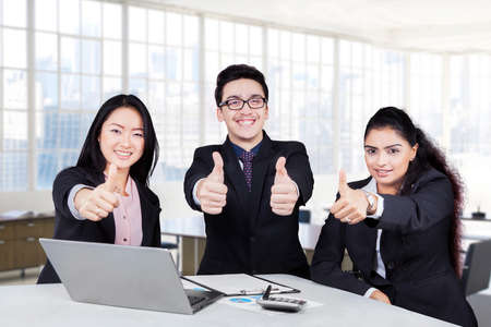Group of multiracial business team showing thumbs up and smiling at the camera in the office photo
