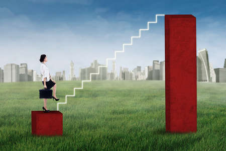 financial obstacle: Businesswoman stepping up on the stair of business graph