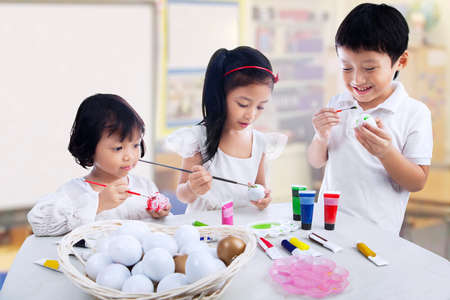asian art: Group of children are painting eggs in art class