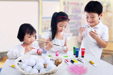 hermanos jugando: Grupo de ni�os est�n pintando los huevos en la clase de arte Foto de archivo