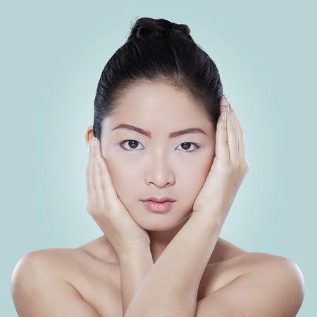 mimos: Chica china joven con la piel sana despu�s de mimar su piel, un disparo en el estudio contra el fondo azul