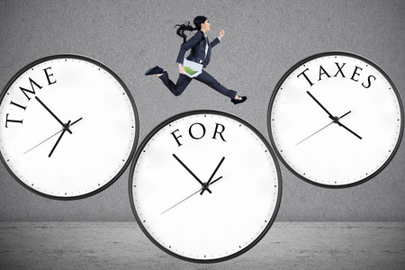 wage: Concept of time for taxes with a businesswoman running on watch Stock Photo