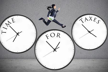 ingresos: Concepto de tiempo para los impuestos con una mujer de negocios que se ejecuta en el reloj