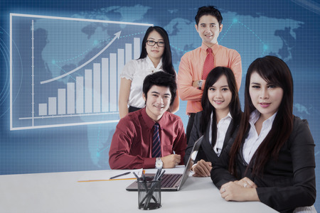 team cooperation: Portrait of young asian business team smiling on camera in the business meeting