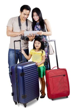 maletas de viaje: Familia alegre que llevar el equipaje a las vacaciones y mirando un mapa en l�nea en la tableta digital