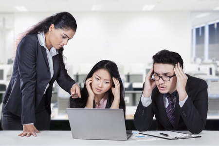 Young female entrepreneur pointing at the laptop to show the mistake of her subordinates