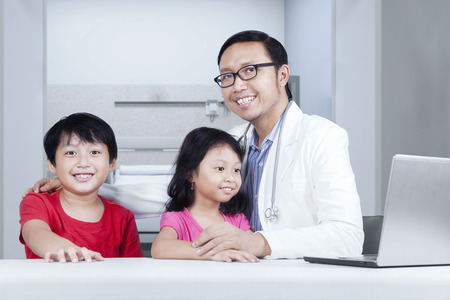 Friendly doctor with children smiling at camera, shot in hospital photo