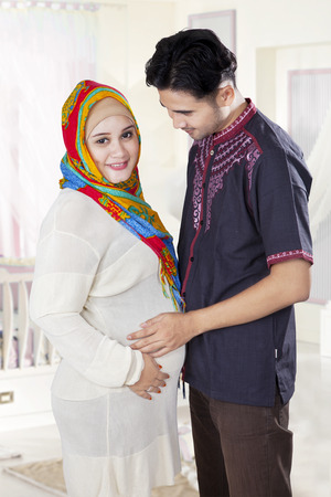 Attractive pregnant woman and her husband standing in the bedroom photo