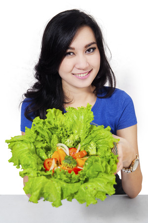 eating healthy: Healthy eating lifestyle concept with beautiful young woman cooking vegetables salad