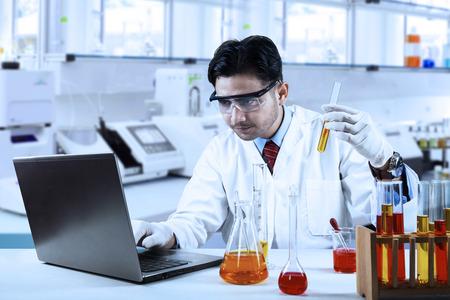 investigando: Científico que hace la investigación con el líquido químico mientras se escribe en la computadora portátil en el laboratorio