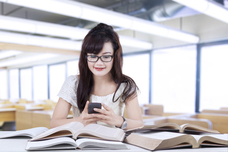 Female student texting while studying in the library photo