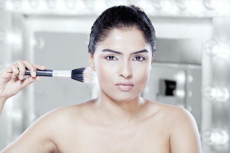 powder room: Portrait of young model with healthy skin apply makeup by brush in the makeup room