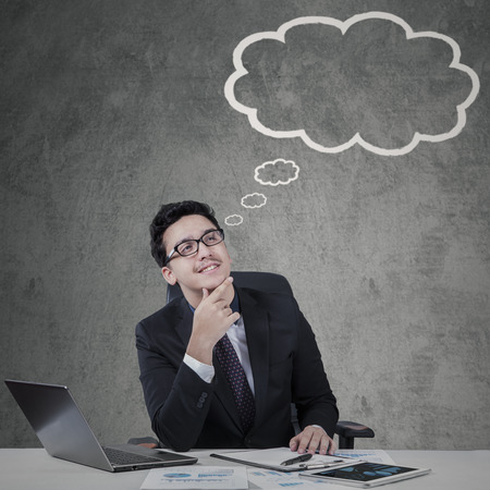 cloud tag: Young caucasian manager daydreaming while looking at empty cloud tag Stock Photo