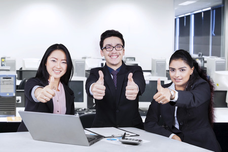 Successful multiracial businesspeopl smiling at the camera while showing thumbs-up in office photo