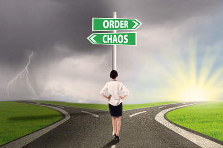order chaos: Businesswoman standing on the road with signpost of order and chaos