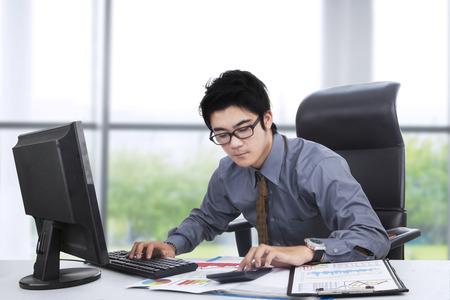 calculadora: Empresario joven que trabaja con la computadora, calculadora, y los documentos en la oficina cerca de la ventana