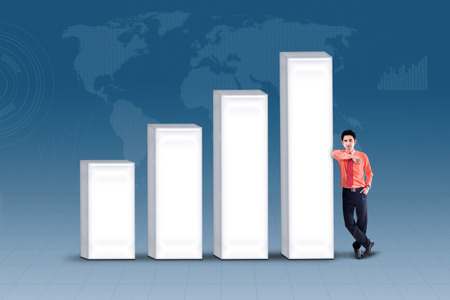 enhancement: Business manager is standing next to bar chart on blue background Stock Photo