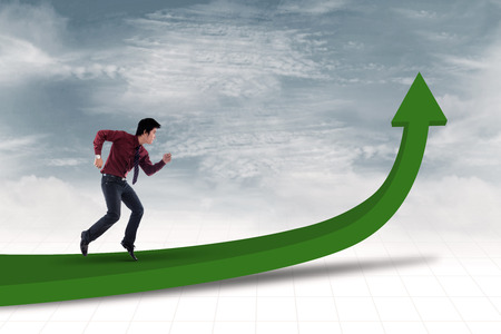 Businessman is running toward the goal to achieve profit under blue sky photo