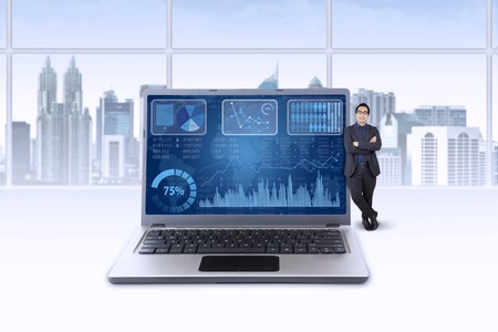 Asian businessman leans on laptop with financial chart on the screen photo