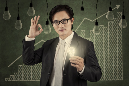 upward graph: Successful businessman holding a bright lightbulb in front of upward graph