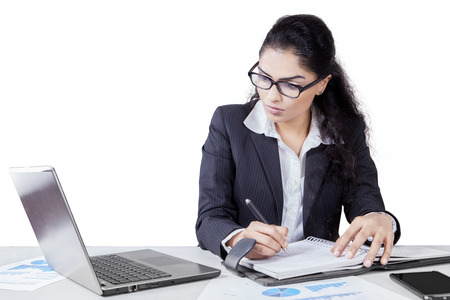 Female worker writes a job schedule on the agenda book while looking at the laptop computer Stock Photo