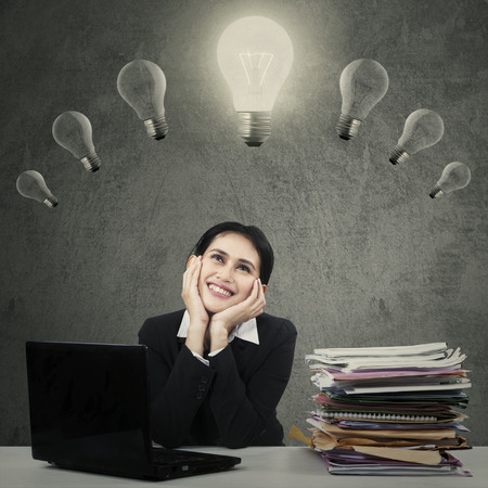 Young female manager working on desk while looking at lightbulb and smiling happy photo