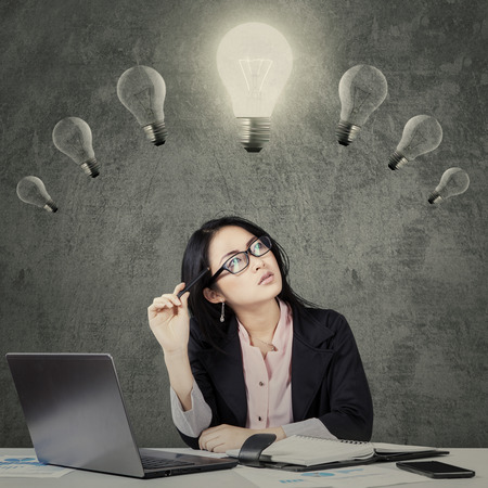 seeking solution: Portrait of young chinese businesswoman thinking an idea while looking at lightbulb over head