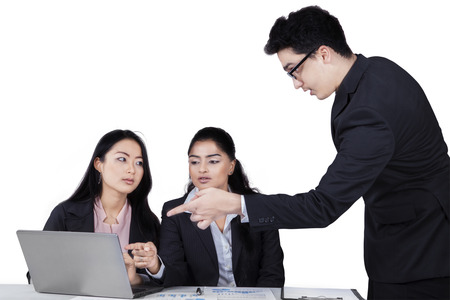 Male business leader pointing at laptop to explain a job on his subordinates, isolated on white photo
